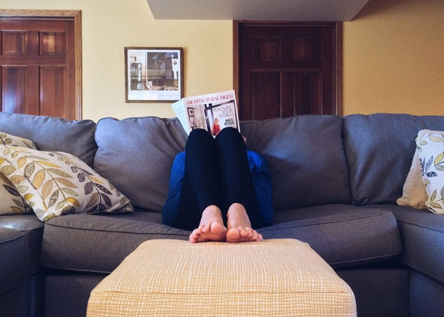 a person reading on a couch with their feet on the stool